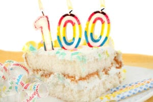 100 birthday candles in a big slice of cake.